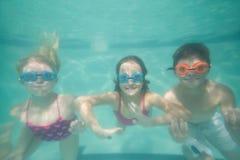 Enfants mignons posant sous l'eau dans la piscine Images stock