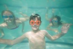 Enfants mignons posant sous l'eau dans la piscine Photo stock