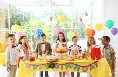 Enfants mignons près de table avec des festins à la fête d'anniversaire à l'intérieur photo stock