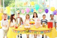 Enfants mignons près de table avec des festins à la fête d'anniversaire à l'intérieur photo libre de droits