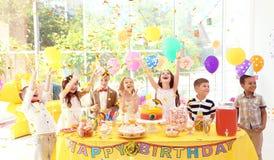 Enfants mignons près de table avec des festins à la fête d'anniversaire à l'intérieur photos libres de droits