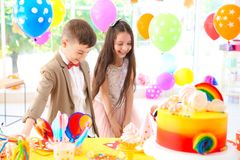 Enfants mignons près de table avec des festins à la fête d'anniversaire à l'intérieur photos stock