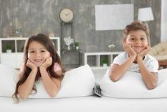 Enfants mignons regardant la TV sur le sofa à la maison Photo stock