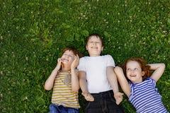 Enfants mignons se reposant sur l'herbe image stock