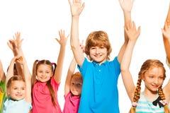Enfants mignons se tenant sur le blanc avec les mains soulevées Images libres de droits