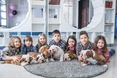 Enfants mignons se trouvant sur le plancher avec le bouledogue de l'anglais de chiots Photo libre de droits