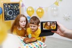 Enfants mignons soufflant les bougies photographie stock