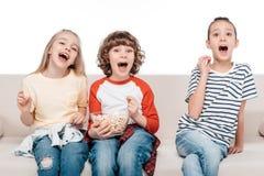 Enfants mignons sur le divan avec le maïs éclaté Photo stock