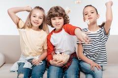 Enfants mignons sur le divan avec le maïs éclaté Photos libres de droits