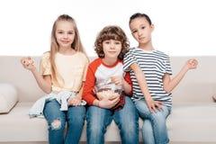 Enfants mignons sur le divan avec le maïs éclaté Images stock