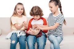 Enfants mignons sur le divan avec le maïs éclaté Photo libre de droits