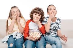 Enfants mignons sur le divan avec le maïs éclaté Photographie stock