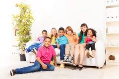 Enfants mignons sur un divan Photo stock