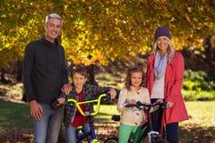 Enfants montant des bicyclettes avec des parents au parc Photographie stock