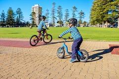 Enfants montant des bicyclettes dans Glenelg images stock