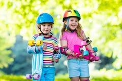 Enfants montant la planche à roulettes en parc d'été Photographie stock