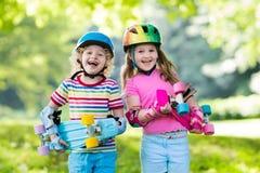Enfants montant la planche à roulettes en parc d'été Photos stock