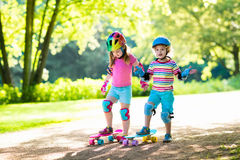 Enfants montant la planche à roulettes en parc d'été Images libres de droits