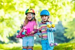 Enfants montant la planche à roulettes en parc d'été Photographie stock libre de droits