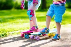 Enfants montant la planche à roulettes en parc d'été Photos libres de droits