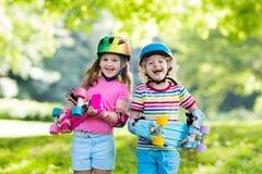 Enfants montant la planche à roulettes en parc d'été Photo stock