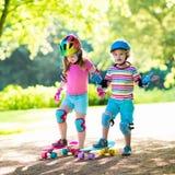 Enfants montant la planche à roulettes en parc d'été Images stock