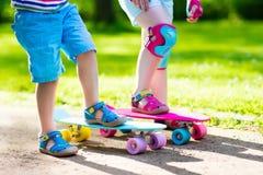 Enfants montant la planche à roulettes en parc d'été Image stock