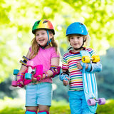 Enfants montant la planche à roulettes en parc d'été Image libre de droits