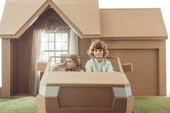 enfants montant la voiture de carton dans l'avant Photographie stock libre de droits