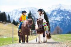 Enfants montant le poney Enfant sur le cheval en montagnes d'Alpes Photographie stock libre de droits