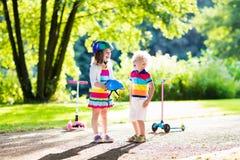 Enfants montant le scooter en parc d'été Photographie stock