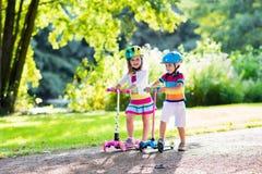 Enfants montant le scooter en parc d'été Photo libre de droits