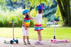 Enfants montant le scooter en parc d'été Images libres de droits
