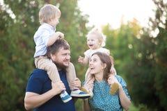 Enfants montant sur des parents en parc Image libre de droits