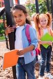 Enfants multi-ethniques avec des livres sur le terrain de jeu Images stock
