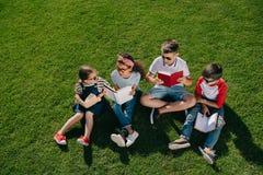 Enfants multi-ethniques dans des livres de lecture de lunettes de soleil sur le pré vert Photo libre de droits