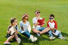 Enfants multi-ethniques dans des livres de lecture de lunettes de soleil tout en se reposant sur l'herbe verte Photos libres de droits