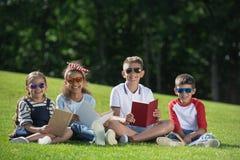 Enfants multi-ethniques de sourire dans des lunettes de soleil tenant des livres et souriant à l'appareil-photo en parc Photographie stock