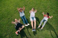 Enfants multi-ethniques gais ondulant à l'appareil-photo avec des mains tout en se reposant sur le pré vert Photographie stock