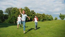 Enfants multi-ethniques heureux jouant ensemble et courant sur le pré vert en parc Photos libres de droits