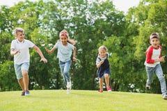 Enfants multi-ethniques heureux jouant et courant ensemble sur l'herbe verte en parc Image stock