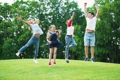 Enfants multi-ethniques heureux jouant et sautant sur le pré vert en parc Image libre de droits