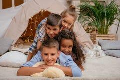 Enfants multi-ethniques heureux se situant en pyramide ensemble à la maison Photographie stock libre de droits