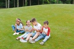 Enfants multi-ethniques jouant avec des bulles de savon tout en se reposant ensemble sur l'herbe Photographie stock libre de droits