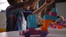 Enfants multi-ethniques jouant avec le constructeur à la classe banque de vidéos