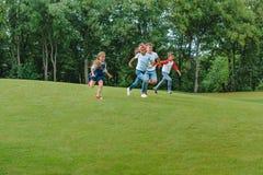 Enfants multi-ethniques jouant ensemble et courant sur l'herbe verte en parc Images libres de droits
