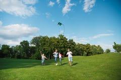 Enfants multi-ethniques jouant ensemble tout en courant avec le cerf-volant en parc Photo libre de droits