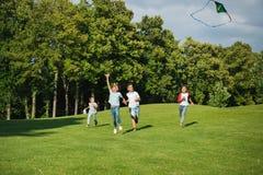 Enfants multi-ethniques jouant ensemble tout en courant avec le cerf-volant en parc Photos libres de droits