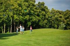 Enfants multi-ethniques jouant ensemble tout en courant avec le cerf-volant en parc Image stock