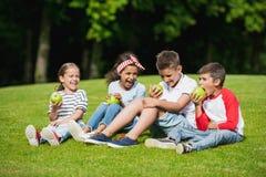 Enfants multi-ethniques mangeant les pommes vertes tout en se reposant ensemble sur l'herbe verte Images libres de droits